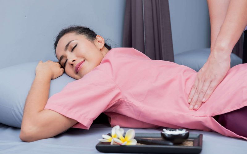 Lady-enjoying-lower-back-TCM-massage-Singapore-therapy-session
