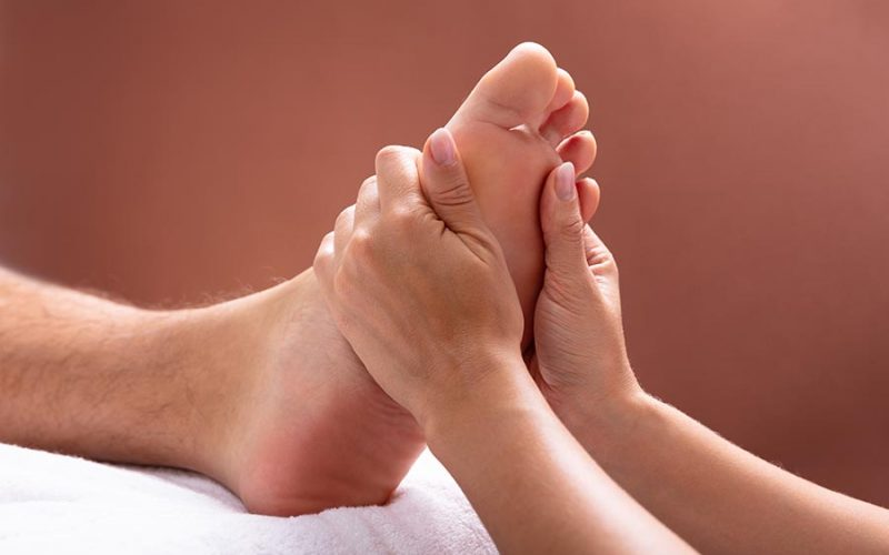 chinese foot massage with two hands pressing against foot