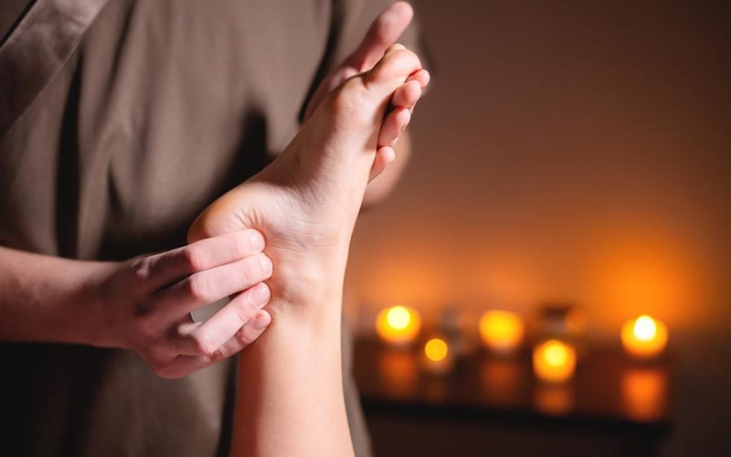 Close-up reflexology foot massage. Male masseur makes foot massage to a female client. Foot Care Concept