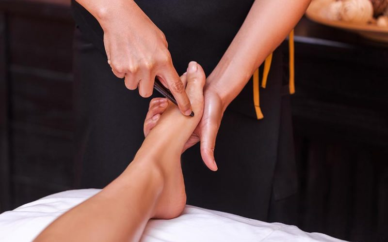 foot reflexology singapore therapist using a stick to relieve tense foot muscles