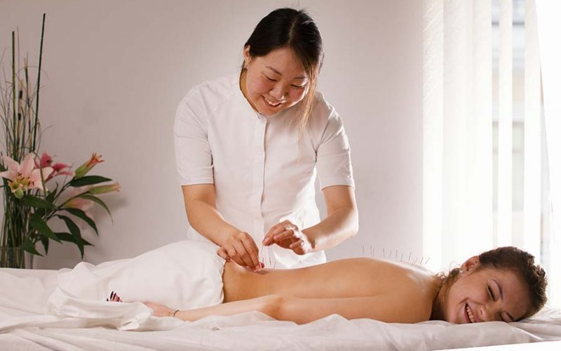 happy lady receiving acupuncture clinic singapore therapy session